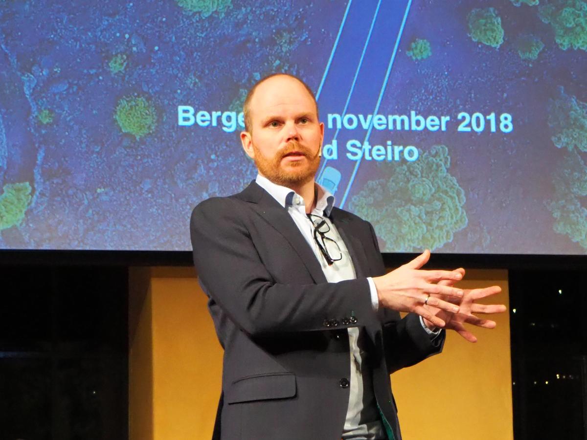 Mann holder foredrag med keynote i bakgrunnen
