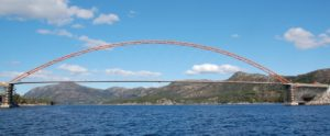 A slender bridge spanning water, mountains in the background