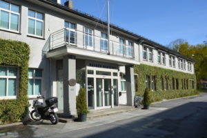 """Grey, partially ivy-covered building, sign over the door says """"Nansen senteret"""". Blue sky"""